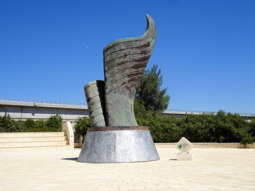 Jerusalem Trail: 9/11 Living Memorial Plaza, close-up showing the sculpture, the flag's thirteen stripes furling in on itself into a flame, Jerusalem-Tel Aviv train bridge in the background - © Deniz Bensason