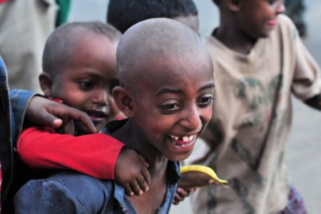 Children of the World: Ethiopia; boy happy carrying his brother on his back
