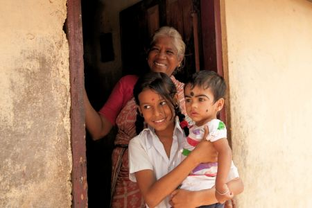 Children of the World: India; Mother and two children at the door