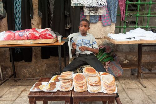 Markets-Vendors - Old City market, Jerusalem, Israel: Ethiopian boy selling Injera (Amharic: እንጀራ)
