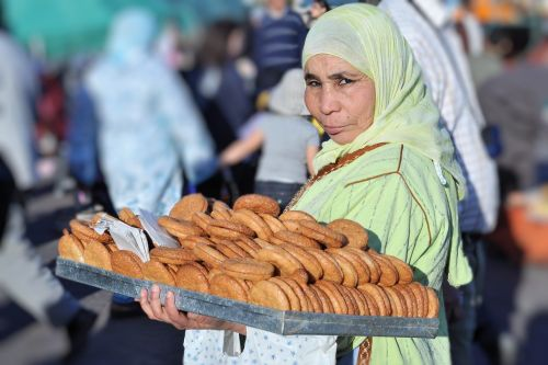 Markets-Vendors - Marrakesh market, Morocco:  Woman selling fekkas (crisp cookies) of a tray