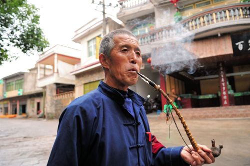 Old-Age – China: Pipe smoking elderly working man