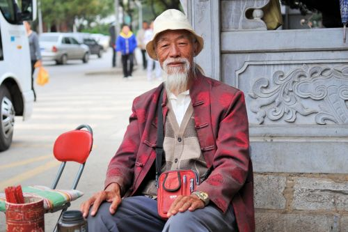 Old-Age – China: Ageing palm reader sitting at the entrance of a temple