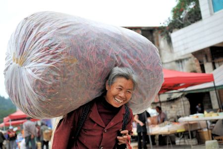 Faces of China: Shizong county market - Woman carrying a lot of hot red peppers