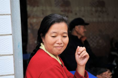 Faces of China: Kunming, Yunnan Province; A shy but smiling woman selling at the market