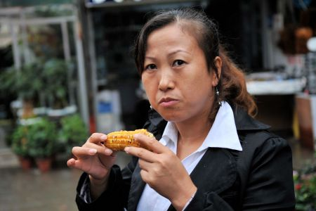 Faces of China: Woman eating corn-on-the-cob in Guiyang market, Guizhou province