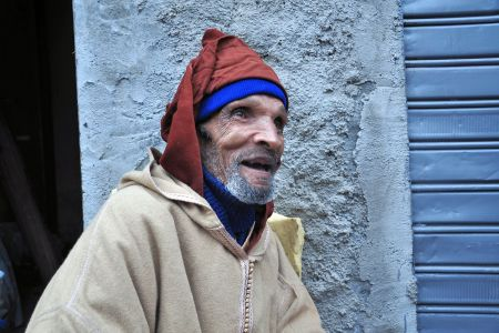 Faces of Morocco: An old toothless man wearing a djellaba, walking