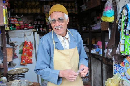 Faces of Morocco: Elderly shopkeeper in his grocery store receiving money from a client