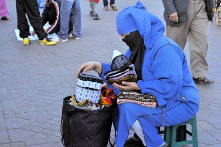 Faces of Morocco: Veiled woman in blue - selling kitchen-cloths in the middle of the market