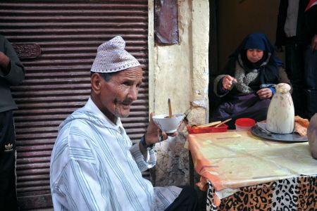 Faces of Morocco: An aging man drinking his soup and an elderly woman drinking tea on the steps of the eatery